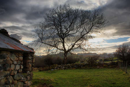 a disused barn in front of a moody sky over a mountain Stock Photo - 13219128