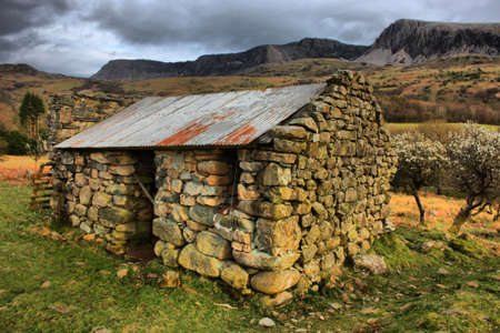 a disused barn in front of a moody sky over a mountain Stock Photo - 13219130