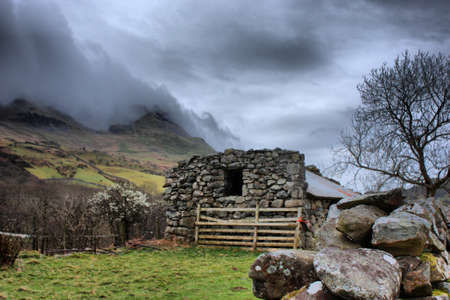 a disused barn in front of a moody sky over a mountain Stock Photo - 13204330