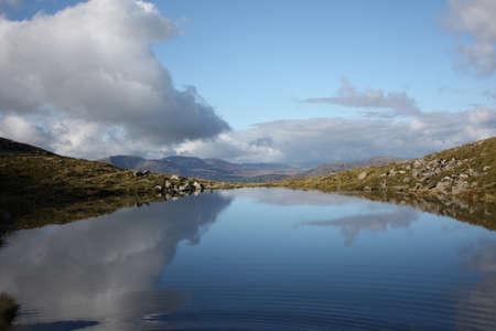 澄んだ青い山の湖で雲の反射