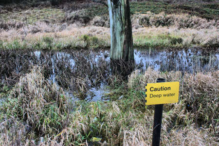 caution deep water sign in front of marshland Stock Photo - 18194299