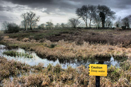 caution deep water sign in front of marshland Stock Photo - 18194297