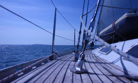 view along the teak deck of a sailing yacht looking out to sea Stock Photo