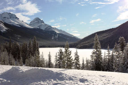 wintery day: a frozen lake in front of a mountain in the rockies under blue sky