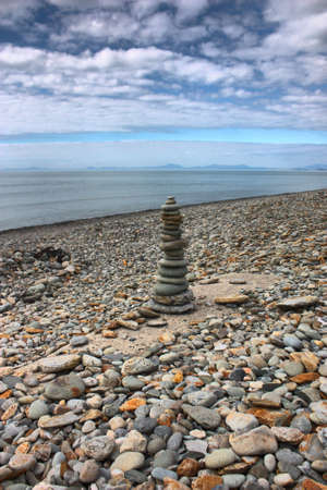 precarious: stones balancing on top of each to make a tower on a beach