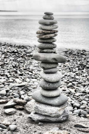 stones balancing on top of each to make a tower on a beach