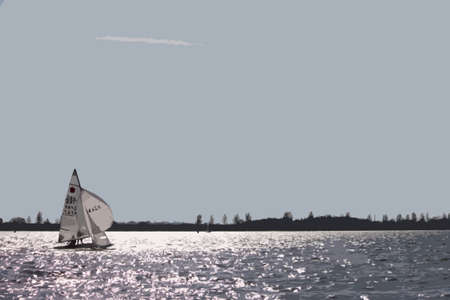 Dinghy sailboat sailing on a lake under a blue sky Illustration