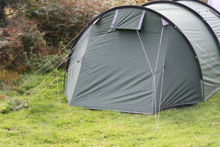 camping pitch: a green tent pitched on grass Stock Photo