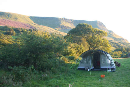 pitched: Tent pitched in front of a mountain range