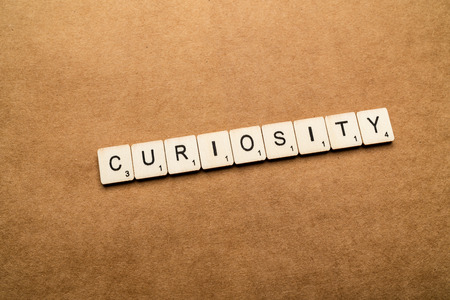 LONDON, UK - May 24 2019: The word CURIOSITY, spelt with wooden letter tiles over a brown textured background