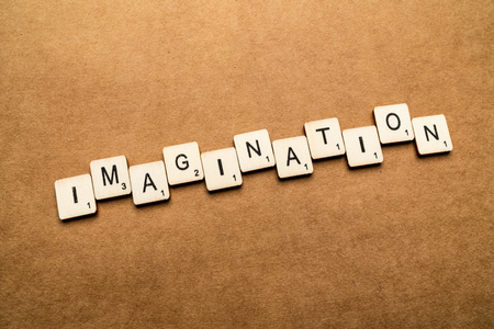 LONDON, UK - May 24 2019: The word IMAGINATION, spelt with wooden letter tiles over a brown textured background