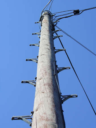 telegraaf: opwaartse oog van een telegraaf paal tegen de blauwe hemel Stockfoto