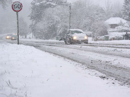 cars driving down a road covered in snow photo