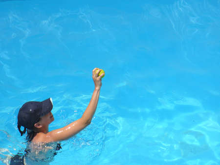 lady catching a tennis ball in a patterned swimming pool photo