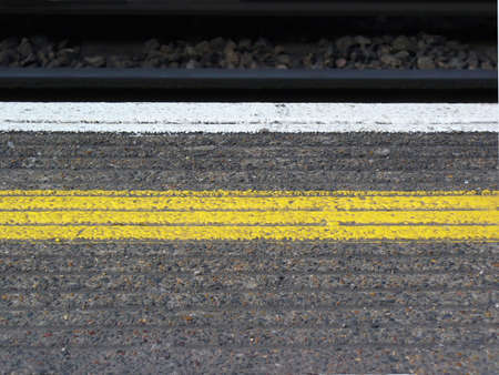 yellow saftey line painted on a train station platform in london, england photo