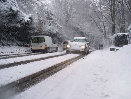 Cars driving on a snow covered road while snow falls in winter