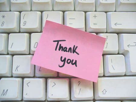 thank you message post-it note on a computer keyboard photo