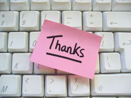 in need: message of thanks post-it note on a computer keyboard