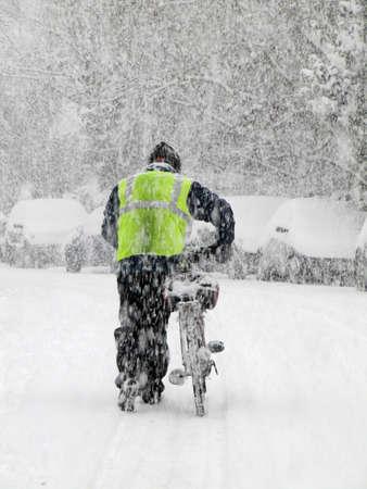 hombre empujando: hombre empujando una bicicleta durante fuertes nevadas en invierno