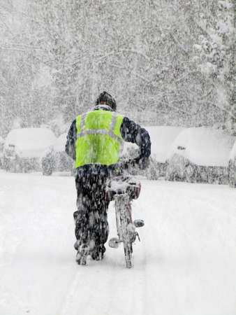snowing: man pushing a bicycle during heavy snow in winter