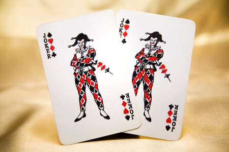 2 joker playing cards on a gold background