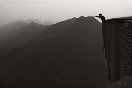 Reaching the mountains - A person in the foreground stretching out here arm to a fare away mountain range. Stock Photo