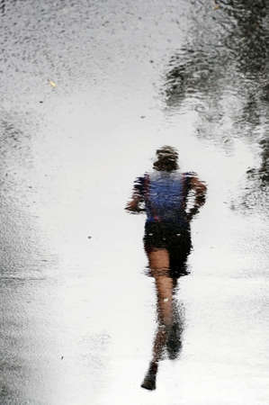 Reflection of a runner - Image with special effect, the reflection of a runner giving the impression that he is hovering over the pavement. Stock Photo