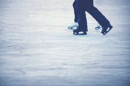 Ice skating couple - Legs of woman and man with white and black skates. Stock Photo