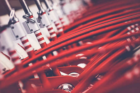 Many red bicycles - City bikes are neatly lined up and ready for rent. Image showing detail and is mainly red colored.