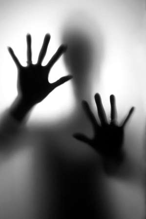Person in fear - Silhouette of a woman, defending her self with here hands. Stock Photo