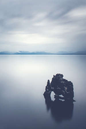 Rock in the calm sea - The Servitude rock in Iceland is a impressive landmark. Legend has it that it is a troll.