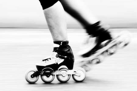 Speed skating - A roller skater is racing down the road, detail of leg and skates.