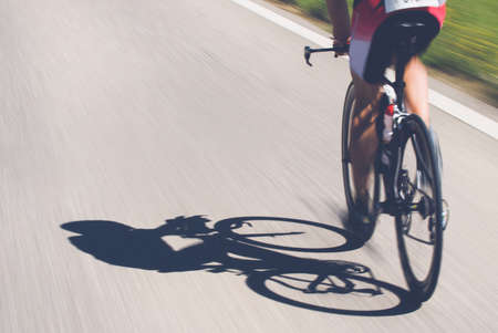 Speedy shadow - A cyclist at top speed on the triathlon race. Stock Photo