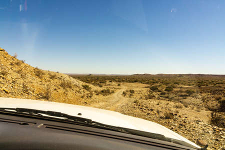 View of a gravel road from inside of a car in the Namib desert, Namib Naukluft National Park