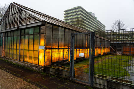 The exterior glass facade of commercial greenhouse translation: entry only for employees of the botanical garden
