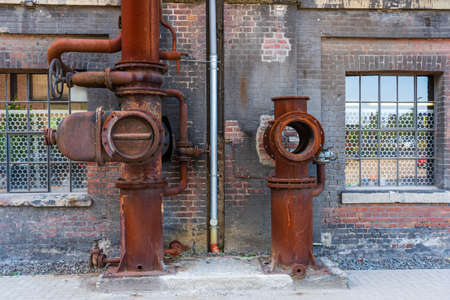 Abandoned industrial building interior. old damaged boiler room. Old rusty industrial pipes. Old control center in the boiler room with pipes and round water taps.