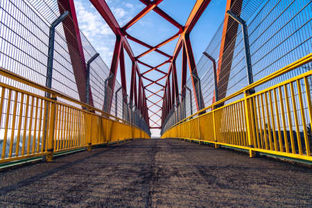 View on small bridge for bikers and pedastrians with steel girders casting shadows on red ground surface of paved path - Netherlands, Roermond 免版税图像