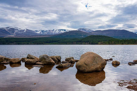 View of the Loch Lomond under a blue sky in a foggy morning with a row of stones and trees reflected on the lake's calm water as the low clouds pass through in the Trossachs National Park, Scotland