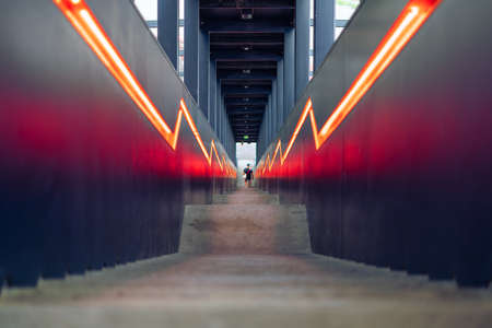 Modern stairs with black boarding and orange lit converging lines in Zollverein, an industrial heritage site in Essen, Germany, a former coal mine Standard-Bild