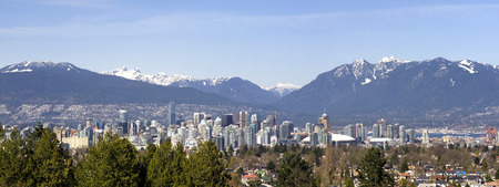 flanked: This image shows a panoramic view of Vancouver, Canada flanked by the North Shore mountains. Stock Photo