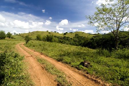 Deze afbeelding toont een rode onverharde weg in de Domonican Republiek Stockfoto