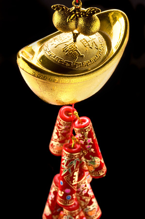 gold ingot: Firecrackers hanging from an Chinese gold ingot.