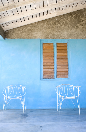 This image shows a couple of wire chairs on a porch in Vinales, Cuba photo