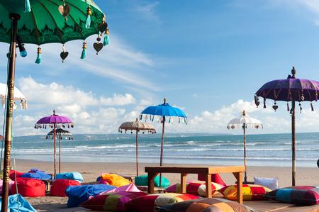 Deze afbeelding toont een aantal kleurrijke strand umbreallas en kussens in Kuta, Bali