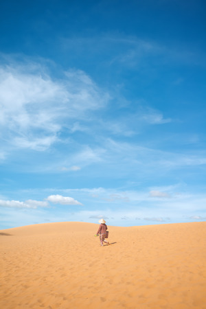 ne: This image shows an unidentified person walking on the red sand dunes. Mui Ne, Vietnam Stock Photo