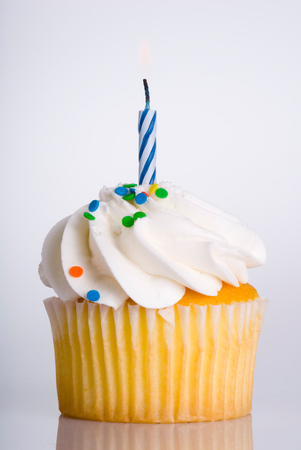 vanilla cupcake: This image shows a Single Vanilla Cupcake with Blue Candle Stock Photo