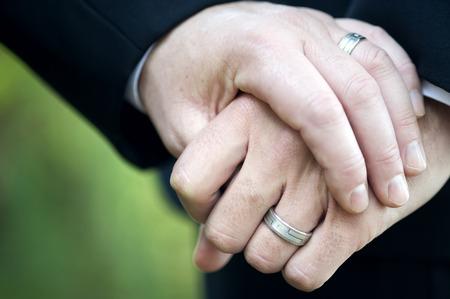 hombres gays: Esta imagen muestra a dos hombres que sostienen la mano que muestran sus anillos de boda.
