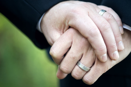 marriages: This image shows two men holding hand displaying their wedding rings.