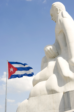 communism: This image shows a statue of jose Marti overlooking the Cuban Flag, Havana, Cuba