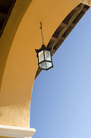 This image shows an old light in a colorful arch - trinidad, Cuba photo